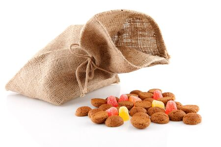 '5 december': bag with typical dutch sweets: pepernoten (ginger nuts) for a celebration at 5 december in the Netherlands over white background