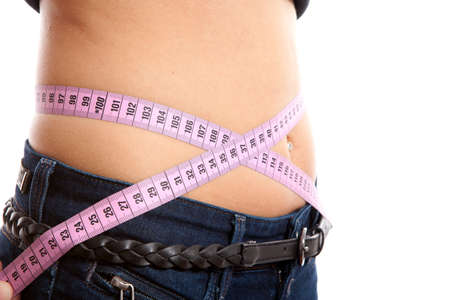 diet, young woman is measuring her waist in closeup over white background photo