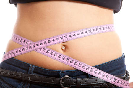 diet, young woman is measuring her waist in closeup over white background Stock Photo - 8409690