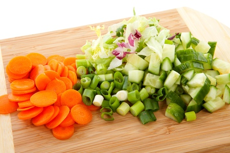 cutting board with sliced vegetables over white background photo
