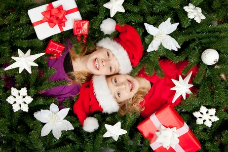 Christmas girls are between the branches of a tree smiling at you Stock Photo