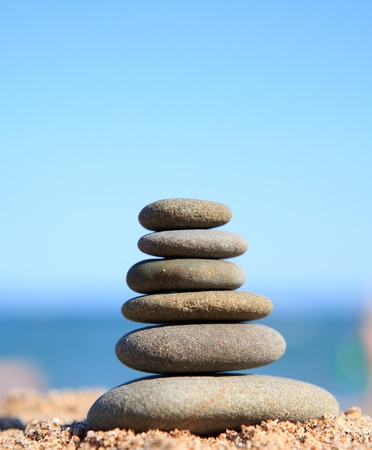 Stack of stones on the beach over blue sky photo