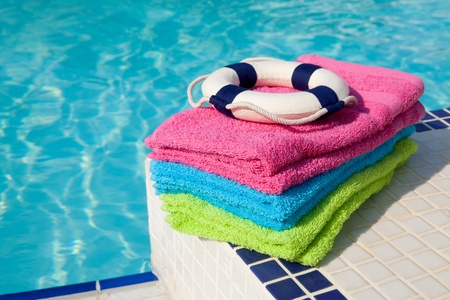colorful towels and life buoy near the swim pool Stock Photo