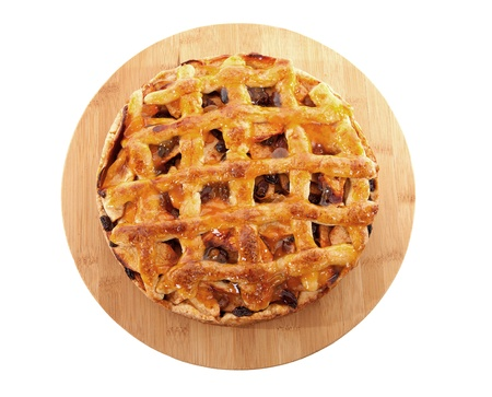 Delicious home baked apple pie on wooden cutting board isolated on white background