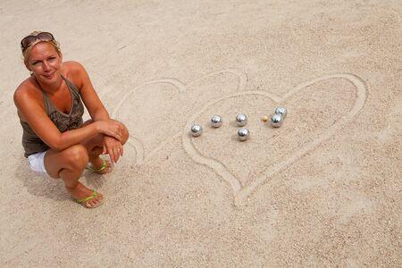 woman loves jeu de boule, posing by balls photo