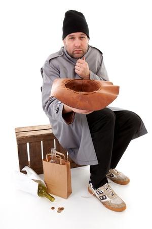 lonelyness: social issue; homeless beggar holding hat for money over white background