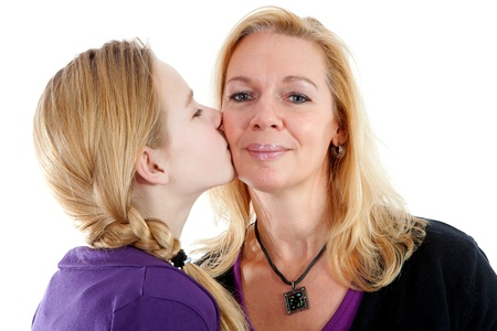 Daughter gives mother a kiss on the cheek over white background photo
