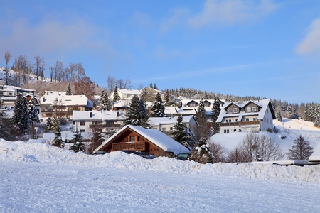 German village in the snow against blue sky photo