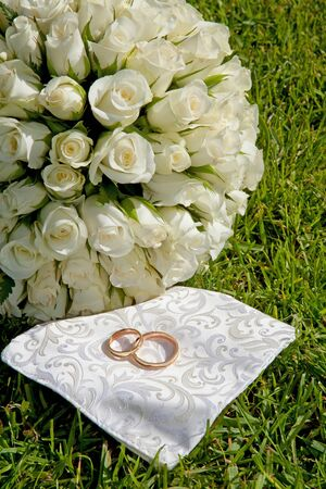 Golden wedding rings and bouquet of roses on grass photo