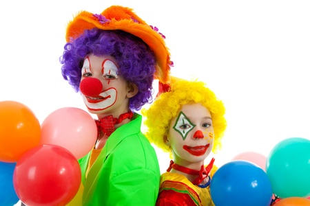 clown's nose: portrait of two children dressed as colorful funny clowns with balloons over white background Stock Photo