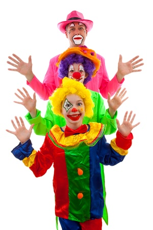 birthday clown: Three people dressed up as colorful funny clowns over white background Stock Photo