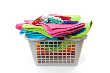 Laundry basket filled with colorful towels and pegs over white background