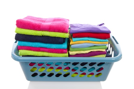 basket filled with colorful folded laundry over white background
