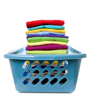 Laundry basket with folded clothes over white background photo