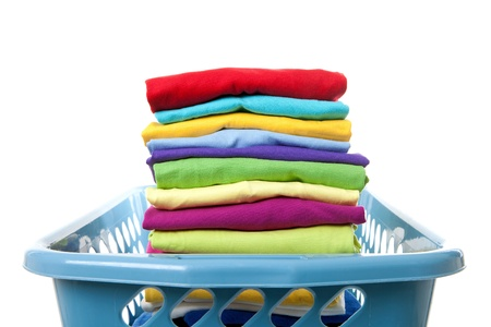 Laundry basket with folded clothes over white background Standard-Bild