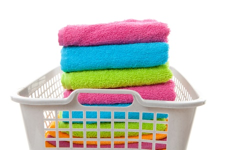 Laundry basket filled with colorful folded towels over white background photo
