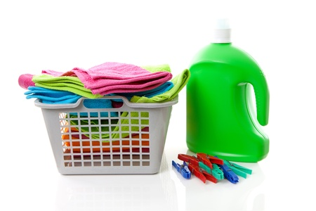 Laundry basket filled with colorful folded towels, pegs and bottle over white background Stock Photo - 8950046