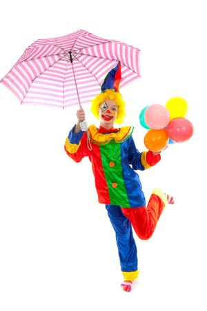 child dressed as colorful funny clown with balloons and umbrella over white background photo