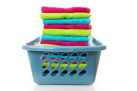 Laundry basket filled with colorful folded towels over white background Stock Photo - 8954092