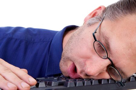 male nerdy geek fall asleep on keyboard in closeup over white background Stock Photo - 9092338
