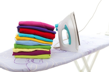 pile of laundry and iron on ironing board over white background