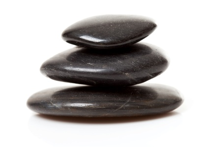 pile of three black pebbles over white background Stock Photo