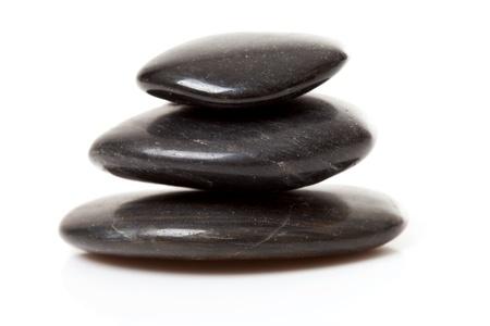over black: pile of three black pebbles over white background Stock Photo