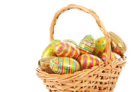 Cane basket with colorful easter eggs over white background