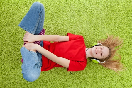 girl is listening to music with headphones on lying in green carpet Stock Photo - 9365305