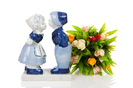 Typical Dutch souvenir in Delft blue and plastic tulips  over white background photo
