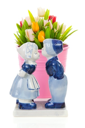 Typical Dutch souvenir in Delft blue and plastic tulips in bucket over white background photo