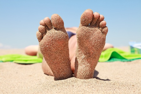 bottom of male feet covered with sand on the beach in sunshine