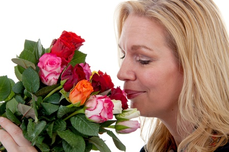 woman is smelling bouquet of colorful roses over white background