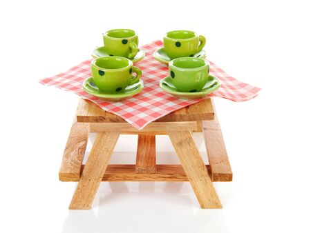 picnic table with green dotted tablewear over white background photo
