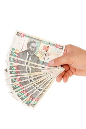 shilling: Hand holding Kenyan currency over white background
