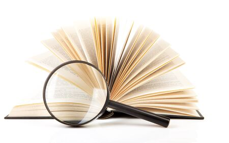 open book with magnifying glass over white background