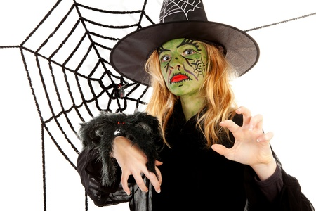 Scary little green witches for Halloween with spiderweb over white background photo