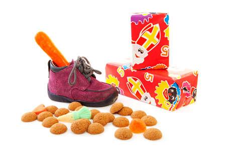 paarse weinig kinderen schoen met presenteert en pepernoten (gember noten), traditionele voor Sinterklaas in Nederland op witte achtergrond