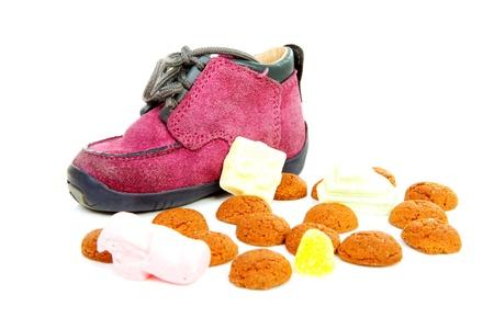 paarse kleine kinderen schoen met pepernoten (gember noten), die traditioneel voor Sinterklaas in Nederland op witte achtergrond