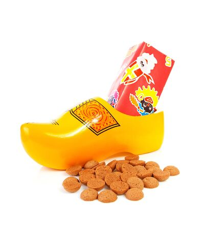 klompen: Dutch wooden shoe with presents and pepernoten over white background