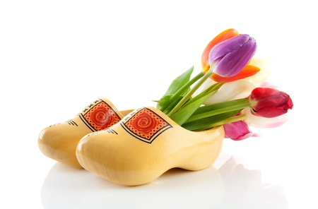 Pair of traditional yellow wooden shoes with colorful tulips isolated on white background Stock Photo - 10875370