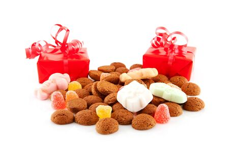 '5 december': Typical dutch sweets: pepernoten (ginger nuts) and presents for celebration at 5 december in the Netherlands over white background