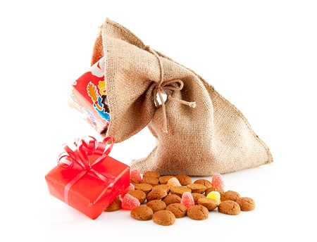 ginger nuts: Typical Dutch celebration: Sinterklaas with surprises in bag and ginger nuts, ready for the kids in december. Isolated on white background Stock Photo