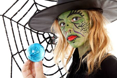 Portrait of green Halloween witch girl in closeup holding big blue marble photo