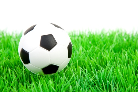 One soccer ball on plastic grass over white background photo