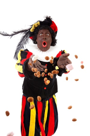Zwarte piet ( black pete) typical Dutch character part of a traditional event celebrating the birthday of Sinterklaas in december over white background throwing pepernoten ( ginger nuts)  Standard-Bild