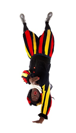 Zwarte piet ( black pete) typical Dutch character part of a traditional event celebrating the birthday of Sinterklaas in december over white background upside down is pointing photo