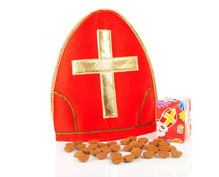 strooigoed: Mitre ( mijter) of Sinterklaas and pepernoten ( ginger nuts), typcal Dutch feast in december over white background