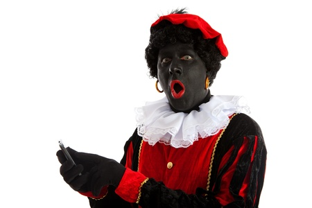 piet: Zwarte piet ( black pete) typical Dutch character part of a traditional event celebrating the birthday of Sinterklaas in december over white background with mobile phone