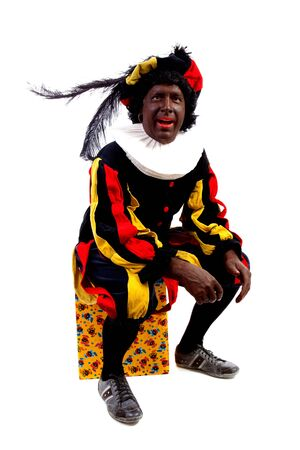 black pete: Zwarte piet ( black pete) typical Dutch character part of a traditional event celebrating the birthday of Sinterklaas in december over white background sitting on present
